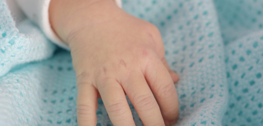 hand of the newborn baby on the blue blanket